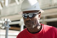 Close-up of a male construction worker with a hardhat and a pair of sunglasses