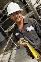 Portrait of a male construction worker holding a tape measure and smiling