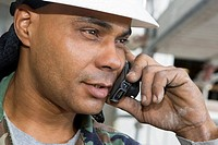 Close-up of a male construction worker talking on a mobile phone
