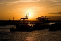 Silhouette of a container ship and cranes at a commercial dock