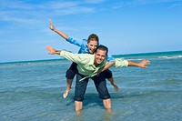 Mid adult woman riding piggyback on a mid adult man with their arms outstretched on the beach