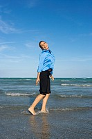 Side profile of a mid adult woman standing on the beach (thumbnail)