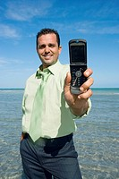 Mid adult man showing a flip phone and smiling