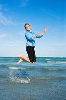 Side profile of a mid adult woman jumping on the beach