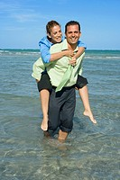 Mid adult woman riding piggyback on a mid adult man on the beach