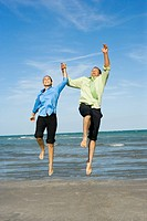 Mid adult couple jumping with holding each other hands on the beach