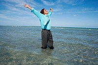 Mid adult man standing on the beach with his arms outstretched