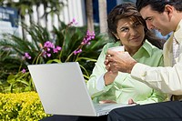 Businesswoman and a businessman sitting in front of a laptop and holding a cup of coffee