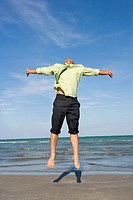 Mid adult man jumping on the beach with his arms outstretched