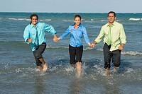 Two mid adult men running with a mid adult woman on the beach