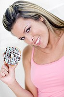 Portrait of a young woman holding a donut and smiling