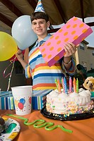 Portrait of a boy holding a birthday present and balloons