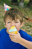 Portrait of a boy eating a cupcake