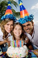 Portrait of a girl with her parents standing in front of a birthday cake and smiling