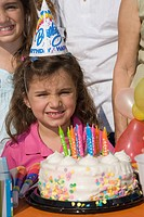 Portrait of a girl with her sisters standing in front of a birthday cake