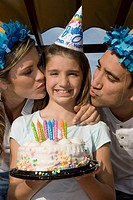 Portrait of a girl holding a birthday cake and her parents kissing her