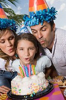 Portrait of a girl with her parents blowing candles on a birthday cake
