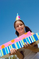 Portrait of a girl holding birthday presents and smiling