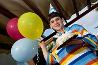 Portrait of a boy holding a birthday cake and balloons