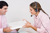 Side profile of a receptionist wearing a headset and receiving a box from a businessman