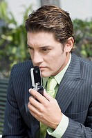 Close-up of a businessman holding a mobile phone and thinking