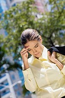 Businesswoman carrying her business suit with her hand on her forehead