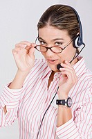 Portrait of a businesswoman adjusting her eyeglasses and a headset (thumbnail)
