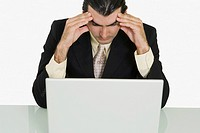 Close-up of a businessman sitting in front of a laptop with his head in his hands