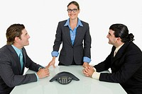 Two businessmen and a businesswoman smiling in a board room