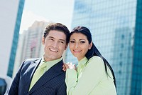 Businesswoman standing with a businessman and smiling