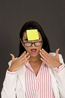 Close-up of a businesswoman looking shocked with an adhesive note in front of her forehead