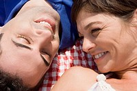 High angle view of a mid adult couple lying on a picnic blanket and smiling