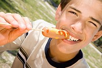 Portrait of a boy eating a sausage