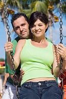 Portrait of a mid adult woman swinging on a swing with a mid adult man standing behind her and smiling