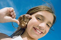 Portrait of a girl holding a conch shell to her ear and smiling