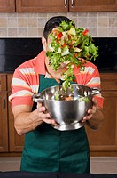 Mid adult man mixing salad in a mixing colander