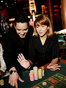 Mid adult man and a young woman gambling in a casino