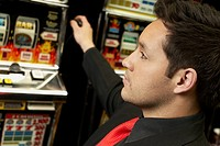 Close-up of a mid adult man playing on a slot machine