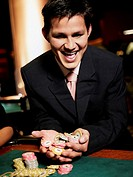 Close-up of a young man cheering with handful of gambling chips in a casino