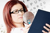 Close-up of a female optometrist examining a report with a magnifying glass
