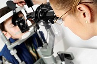 Close-up of a female optometrist examining eyes of a boy