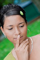 Close-up of a young woman thinking with her finger on her lips