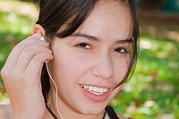 Portrait of a young woman holding an earbud and smiling