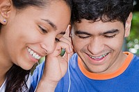 Close-up of a young woman and a mid adult man listening to music and smiling