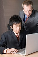 Businessmen looking at laptop computer