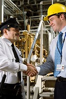 Security guard shaking hands with manager in waste treatment plant