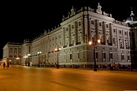Lampposts lit up in front of a palace lit up at night, Madrid Royal Palace, Madrid, Spain