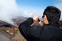 Rear view of a young man taking a photograph, Haleakala National Park, Maui, Hawaii Islands, USA