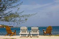Four deck chairs on the beach, Dixon Cove, Roatan, Bay Islands, Honduras