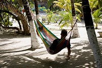Rear view of a man lying in a hammock, Coral Cay, Dixon Cove, Roatan, Bay Islands, Honduras